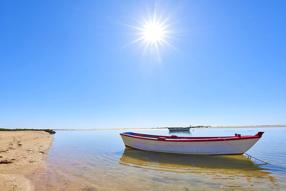 The sun shines above a small fishing boat on transparent lagoon water in Cacela Velha, Algarve, Portugal.