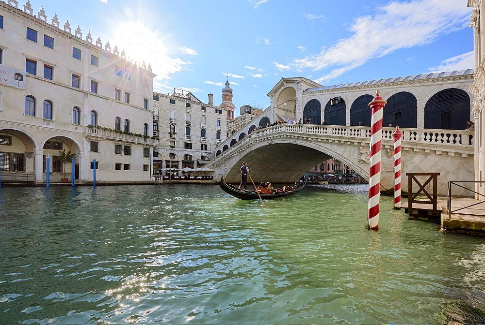 A gondolier rowing under Rialto Bridge in Venice, UNESCO World Heritage Site, Veneto, Italy, Europe