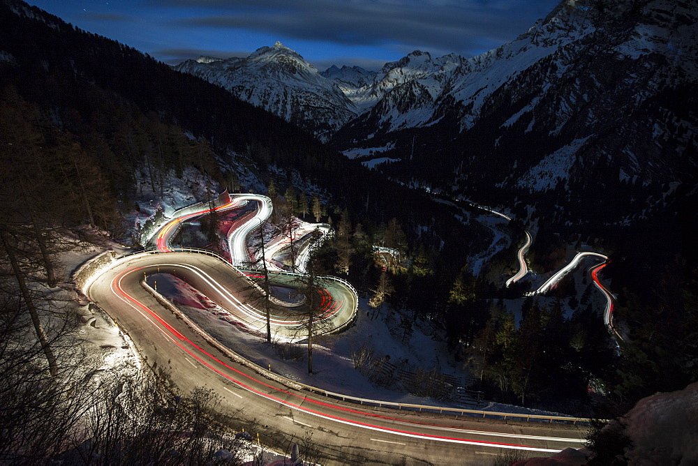 Car lights on the curvy Maloja Pass road at night, Maloja Pass, Engadine, Province of Graubunden, Switzerland, Europe