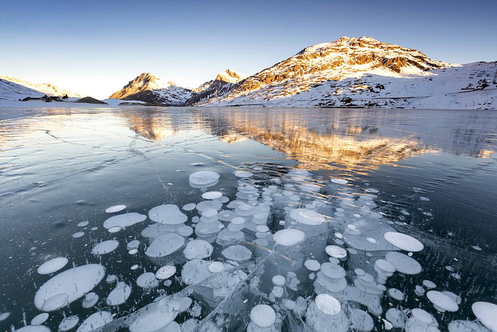Ice bubbles at sunrise. Bianco Lake, Bernina Pass, Engadin, Switzerland.