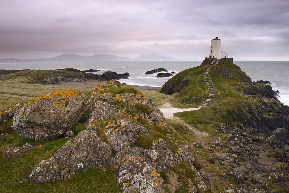 Under a pink, cloudy sky sits the lighthouse at the edge of Llanddwyn Island, Anglesey, Wales.