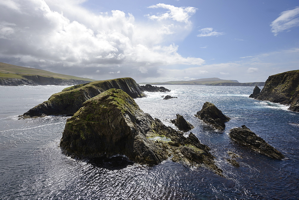 Huge clouds clear the way for bright sunshine to light the cliffs and islands of St. Ninian's Bay, Shetland, Scotland, United Kingdom, Europe