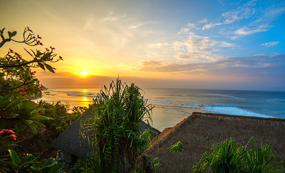 Surfers at sunset in Bali with straw roofed huts, Indonesia, Southeast Asia, Asia