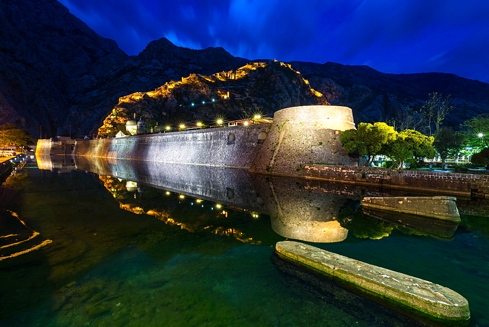 Part of Kotor's old town wall and lit fortress ramparts reflected during the evening blue hour. Montenegro.