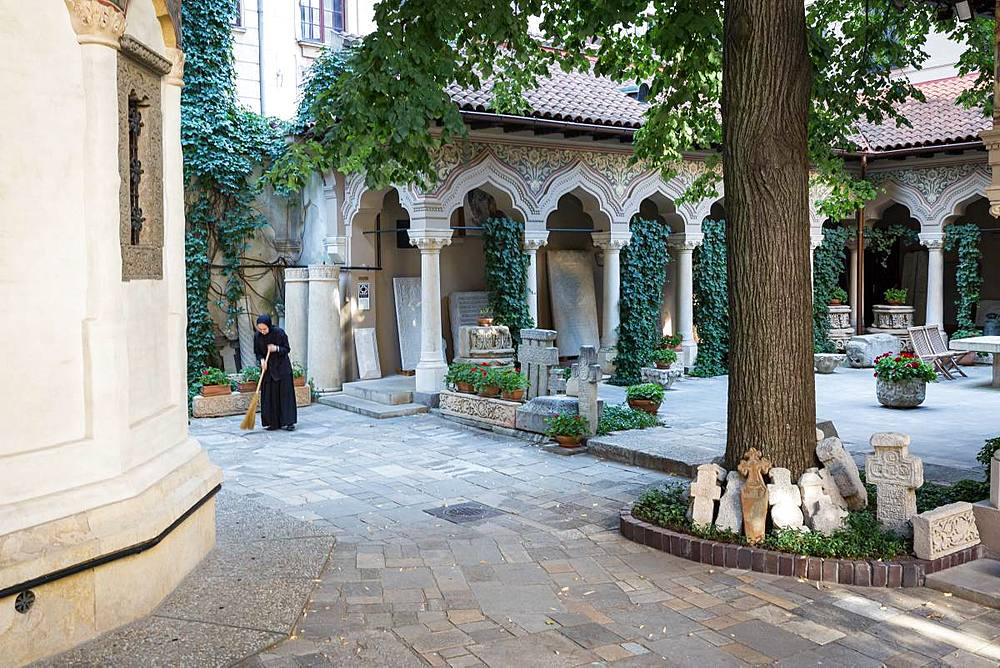 A nun sweeps the grounds of the Stavropoleos Monastery Church (Biserica Manastirea Stavropoleos) early in the morning, Bucharest, Romania, Europe