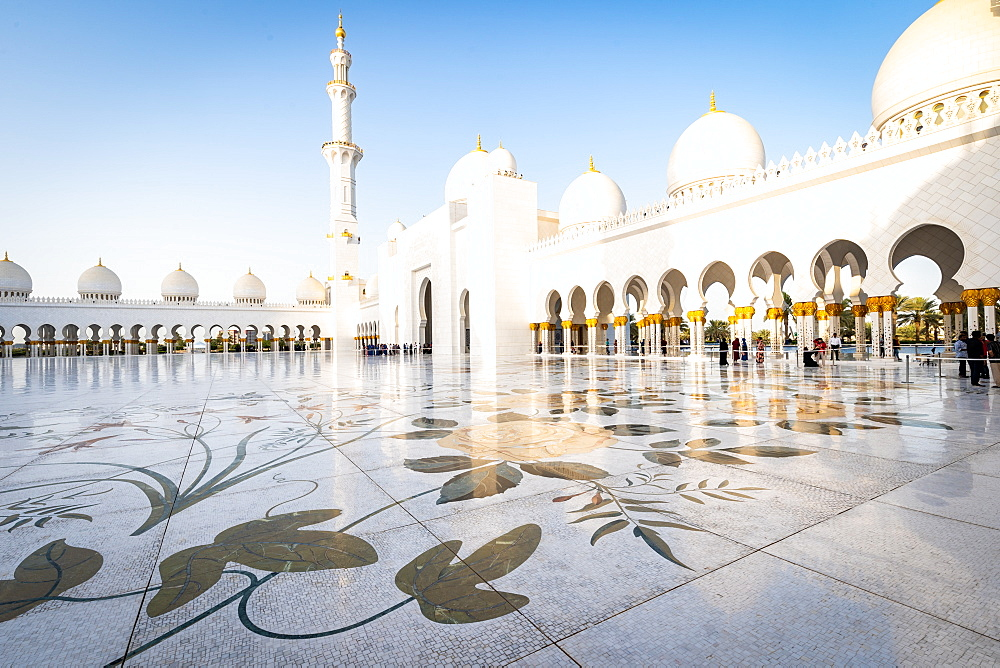The domes and minarets of Abu Dhabi's Grand Mosque viewed across the large marble tiled central courtyard, Abu Dhabi, United Arab Emirates, Middle East