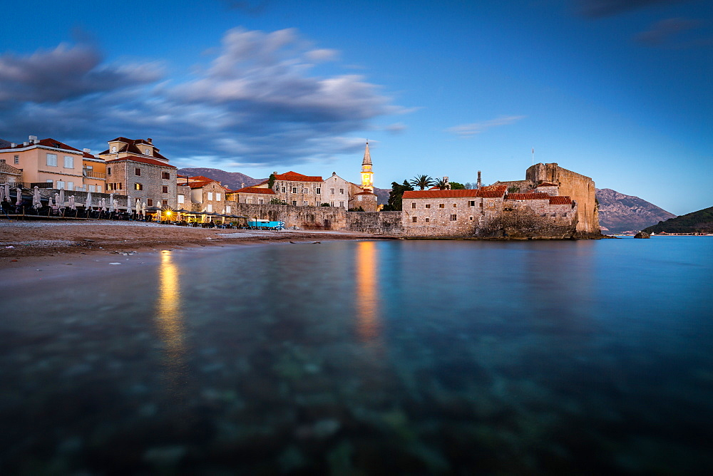 A long exposure during the evening blue hour of the beach and stari grad (old town) of Budva, Montenegro, Europe