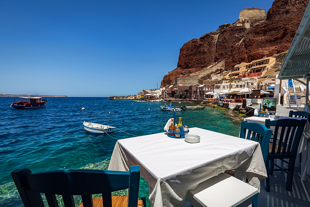 A table with a view at one of the seafood restaurants in Ammoudi Bay (Amoudi) at the bottom of steps below Oia, Santorini, Cyclades, Greek Islands, Greece, Europe