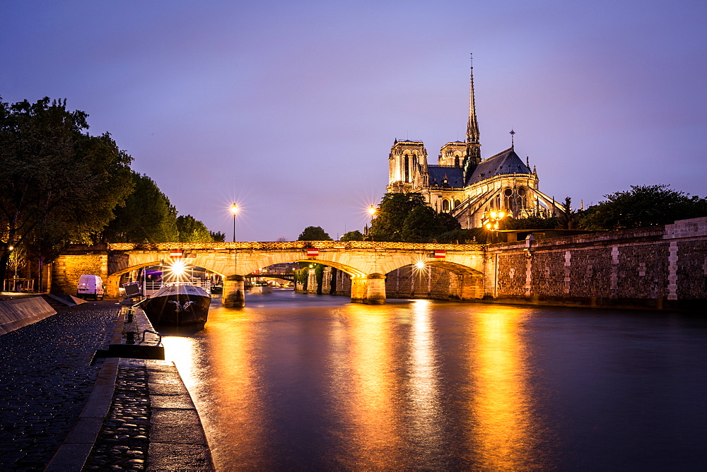 Notre Dame Cathedral and lights reflecting in the Seine on a wet evening in Paris.