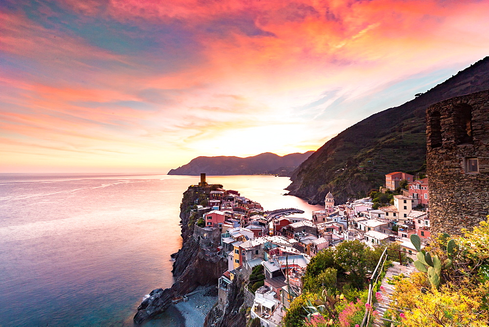 The setting sun lights up the sky and casts an orange glow over the old town and harbour of Vernazza, Cinque Terre, UNESCO World Heritage Site, Liguria, Italy, Europe - 1263-98