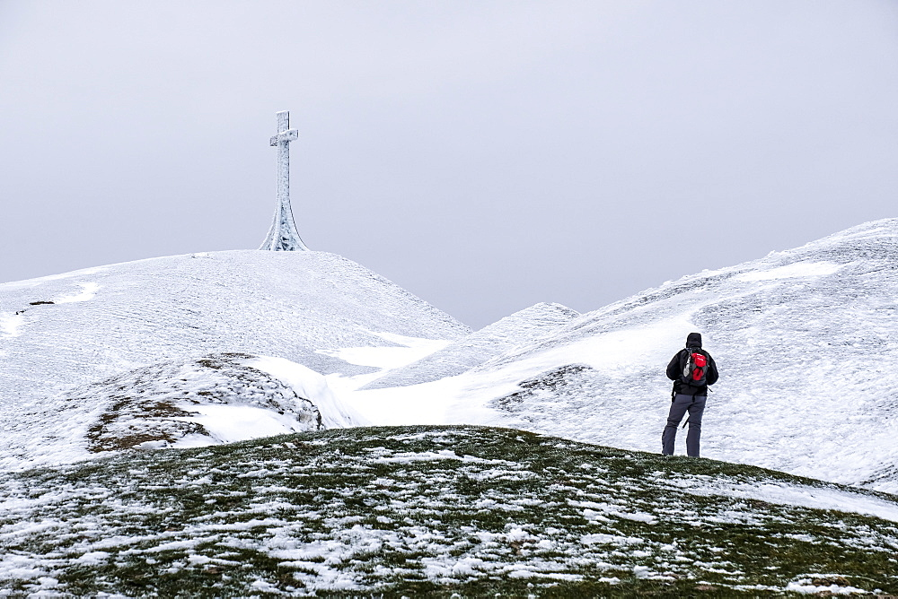 Hiker reaching the summit cross of Monte Catria in winter, Apennines, Umbria, Italy, Europe - 1264-154