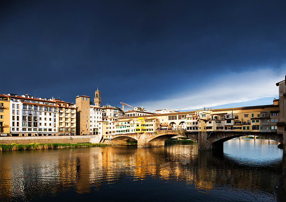 Ponte Vecchio reflecting in the Arno rRver against a dark blue stormy sky, Florence, UNESCO World Heritage Site, Tuscany, Italy, Europe