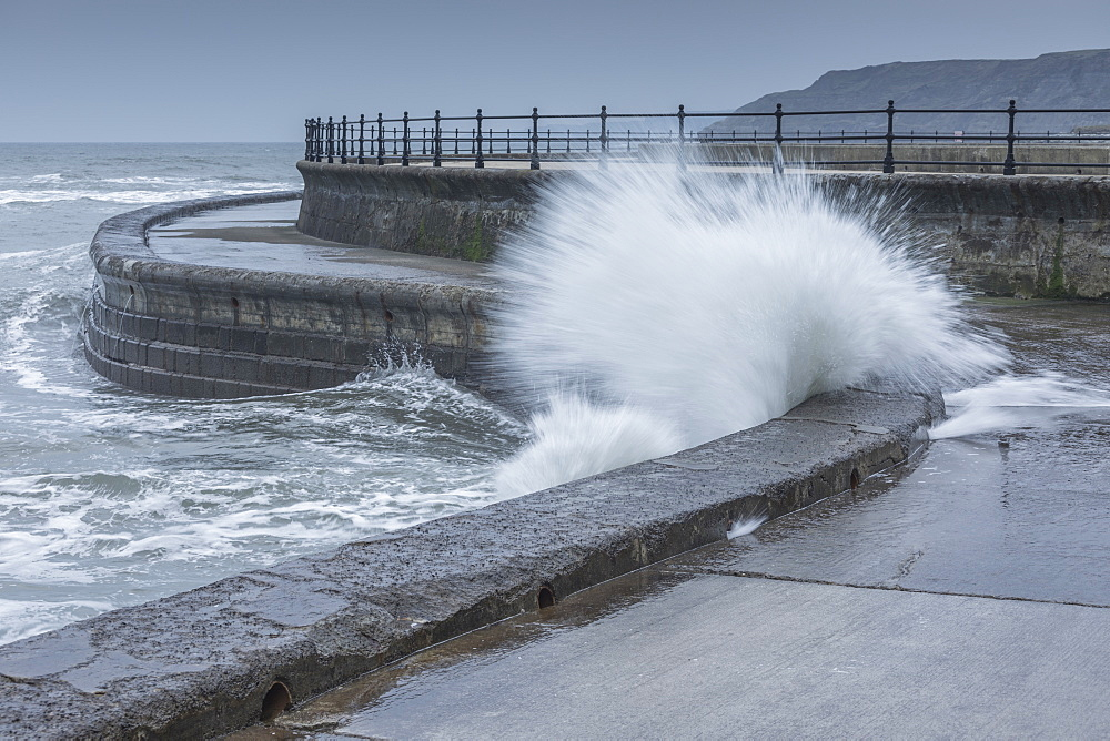 Waves crashing into the sea wall at Scarborough, North Yorkshire, UK