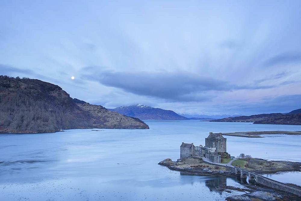 Moon setting at Eilean Donan Castle, Dornie, Kyle of Lochalsh, Western Highlands of Scotland, United Kingdom, Europe