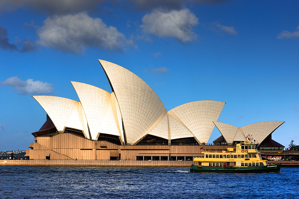Ferry goes past the Sydney Opera House at Golden hour. New South Wales, Australia.