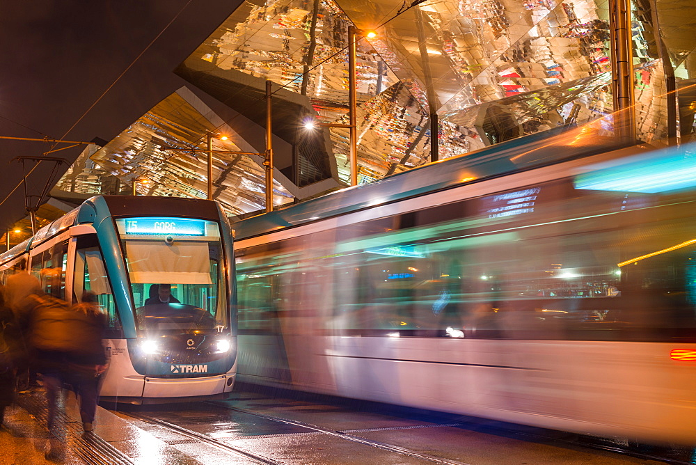 Night view of two trams at Glories station with the dazzling, reflective canopy to the rear, Barcelona, Catalonia, Spain, Europe
