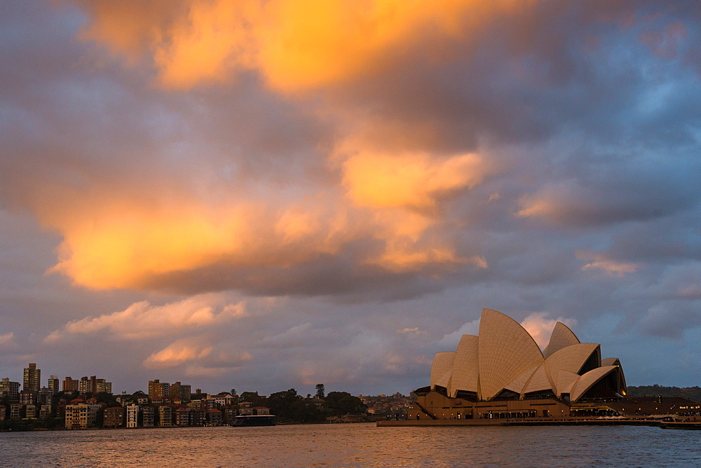 Sydney harbour with dramatic clouds as the sun sets. New South Wales, Australia.