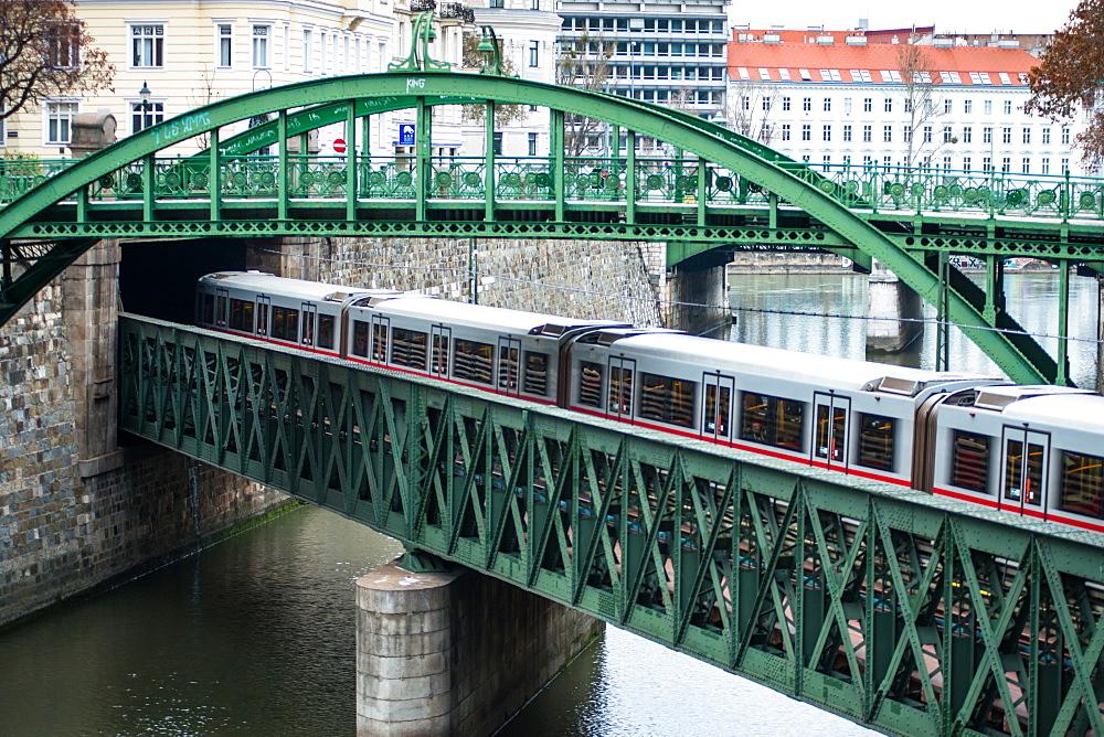 U-Bahn train on Zollamtssteg Arch Bridge with Zollamtsbrücke Truss Bridge in Vienna, Austria.