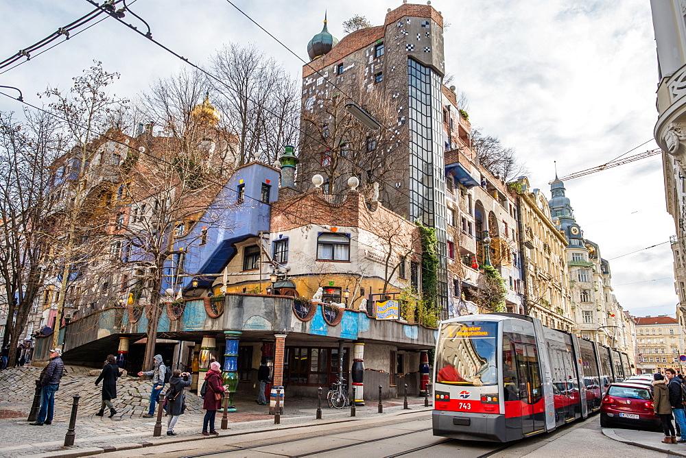 Tram at Hundertwasserhaus, expressionist landmark and public housing, designed by Friedenreich Hundertwasser in Vienna. Austria.