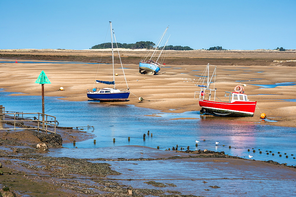 Colourful boats on sandbanks low tide, East Fleet river estuary, Wells next the sea, North Norfolk coast, Norfolk, East Anglia, England, United Kingdom, Europe