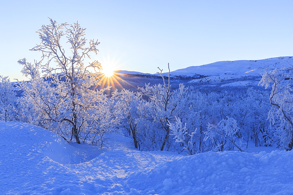 The sun rises from the peaks on the border of Sweden and Norway, Riskgransen, Norbottens Ian, Lapland, Sweden, Scandinavia, Europe - 1269-19