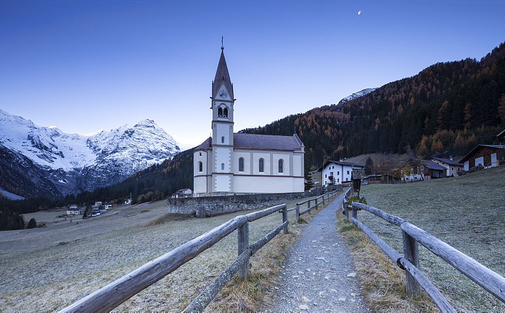 Church of Trafoi during frozen twilight with moon in the sky, Trafoi, Stelvio National Park, Alto Adige-Sudtirol, Italy, Europe - 1269-2