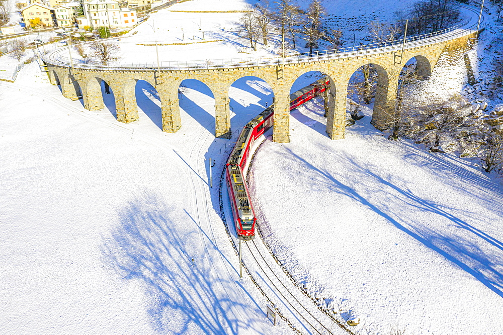 Bernina Express passes under the helical (spiral) viaduct of Brusio, UNESCO World Heritage Site, Valposchiavo, Canton of Graubunden, Switzerland, Europe - 1269-559