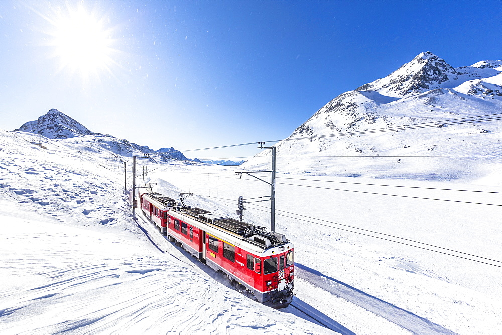 Bernina Express transit along Lago Bianco in winter , Bernina Pass, Engadin, Canton of Graubunden, Switzerland, Europe.