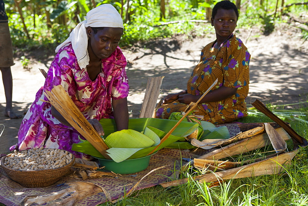 A woman wraps some groundnuts in a banana leaf. - 1270-107
