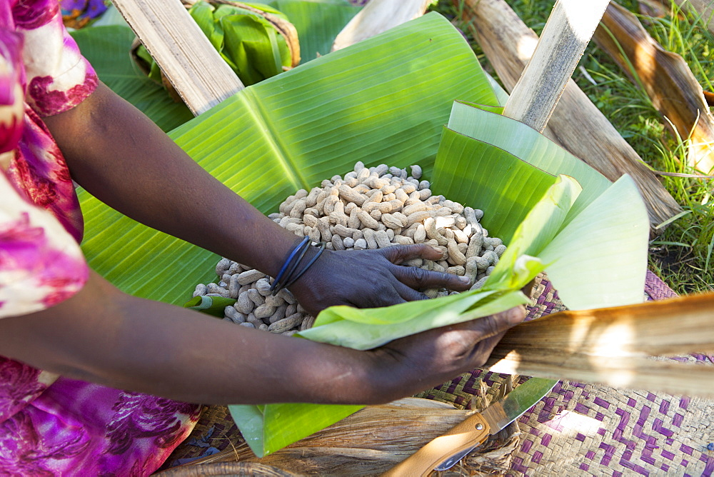 A woman wraps some groundnuts in a banana leaf. - 1270-108