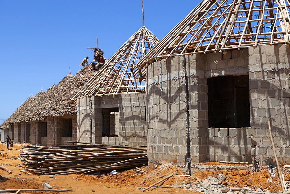 Men thatching the roofs of new houses, Mtwara, Tanzania, East Africa, Africa