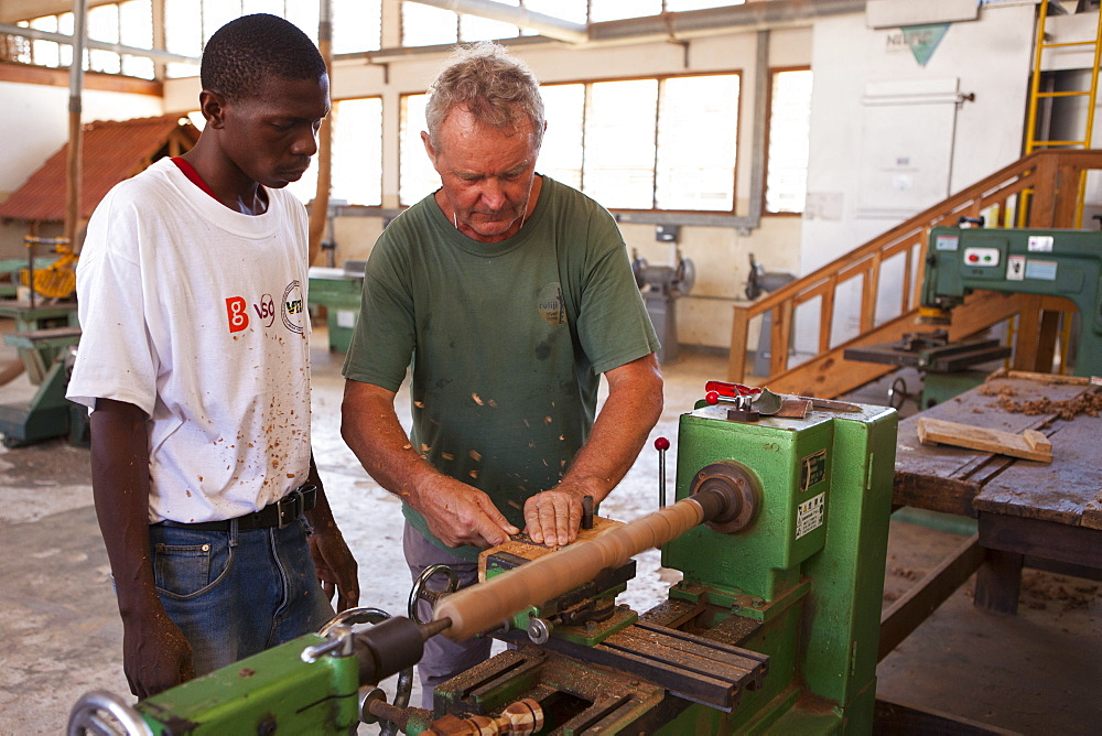 A VSO volunteer teaching how to use a lathe during a VSO woodwork vocational skills training workshop, Tanzania, East Africa, Africa - 1270-122