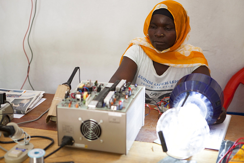 A female solar engineer, known as a solar mama, using a soldering iron to fix the printed circuit board of a solar lamp, Tanzania, East Africa, Africa