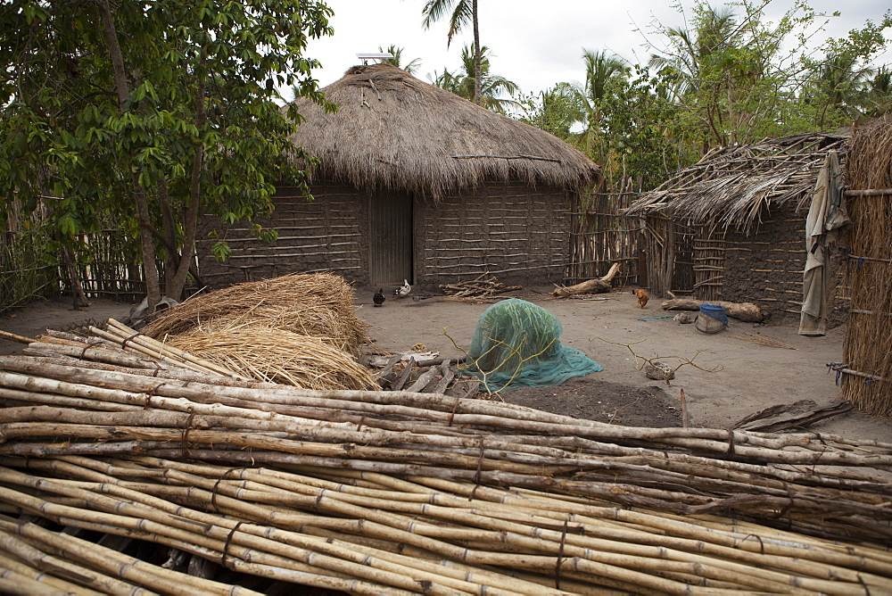 A traditional mud hut home with a thatched roof and a solar panel on the top of it, Tanzania, East Africa, Africa - 1270-126