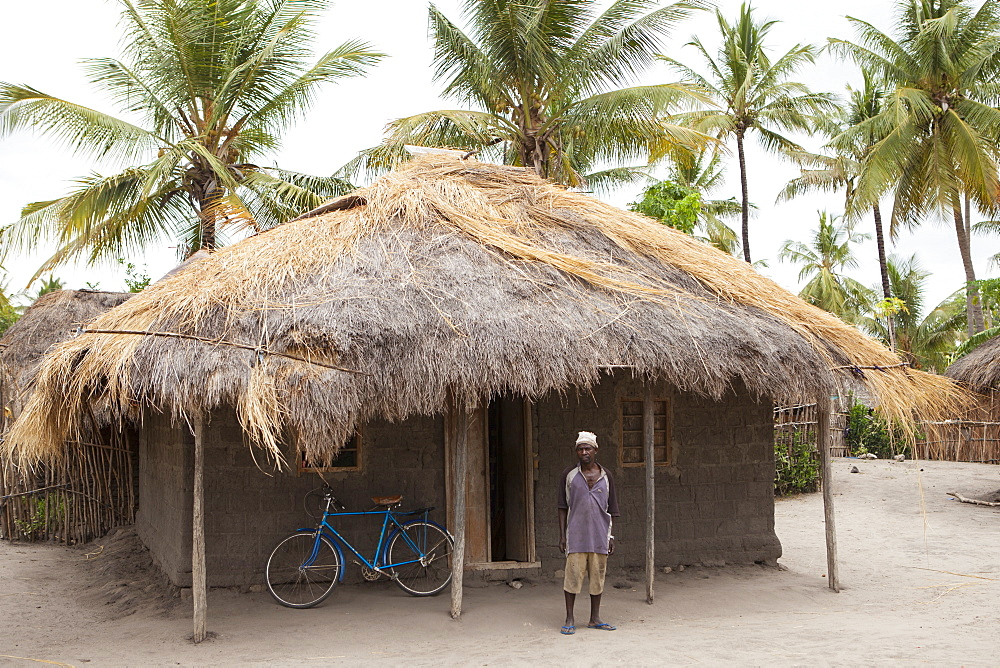 A man stands proudly outside his traditional mud hut home which has just been fitted with a solar panel, Tanzania, East Africa, Africa - 1270-127