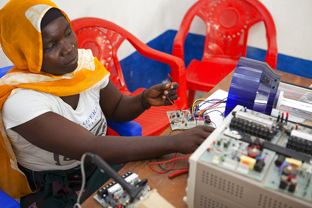A female solar engineer, known as a solar mama, works on the printed circuit board of a solar lamp, Tanzania, East Africa, Africa - 1270-129