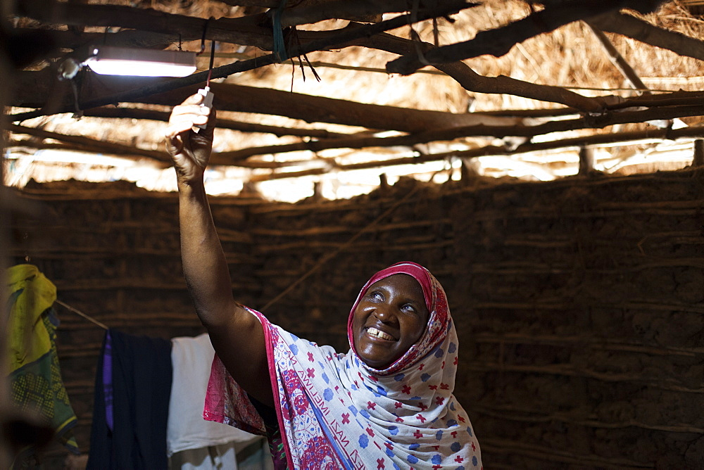 Stock photo of a woman smiling as she turns on the new solar light in her mud hut