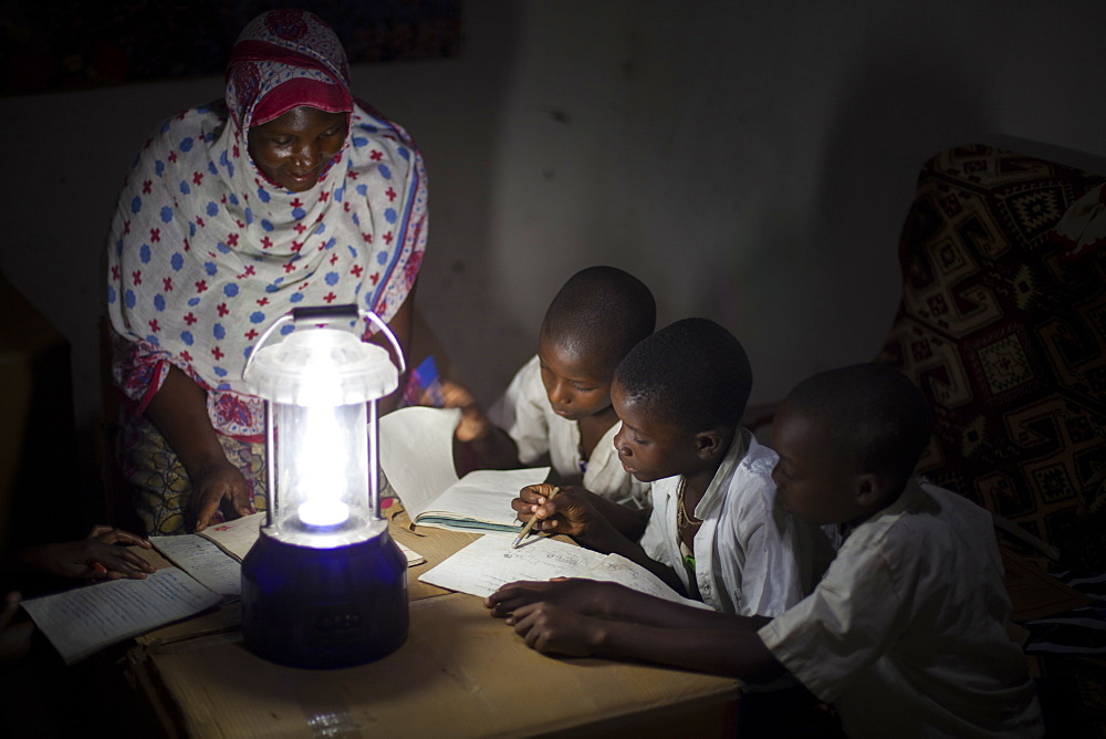 A group of boys read their homework by the light of a solar lantern, Tanzania, East Africa, Africa - 1270-131