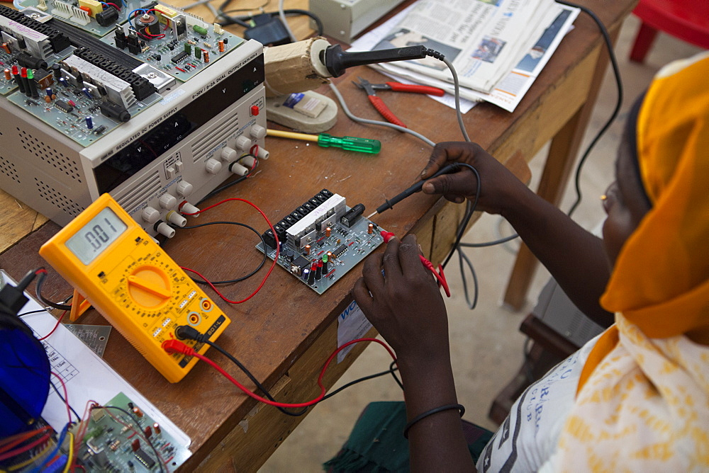 A woman, known as a Solar Mama, fixes a solar circuit board, Tanzania, East Africa, Africa