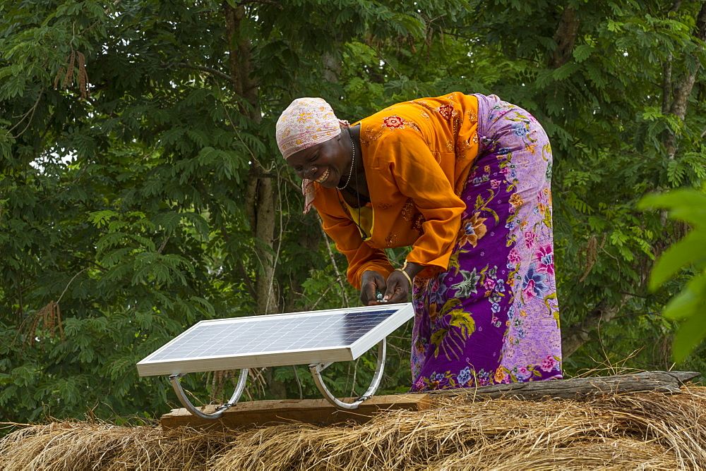 A woman, known as a Solar Mama, fixes a solar panel to the top of a traditional thatched mud hut, Tanzania, East Africa, Africa - 1270-134
