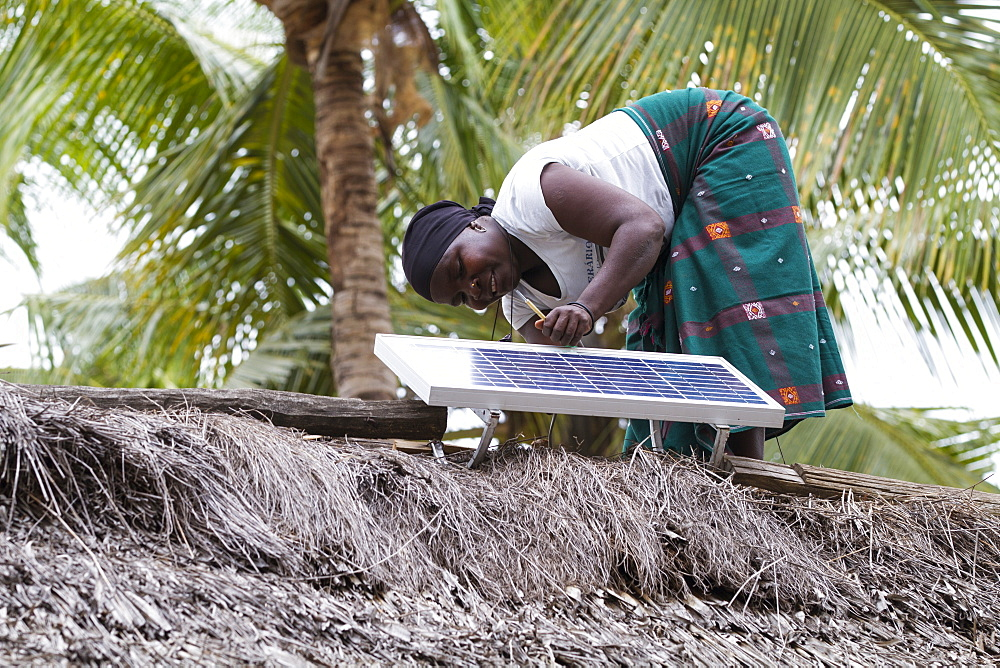 A woman, known as a Solar Mama, fixes a solar panel to the top of a traditional thatched mud hut, Tanzania, East Africa, Africa - 1270-135