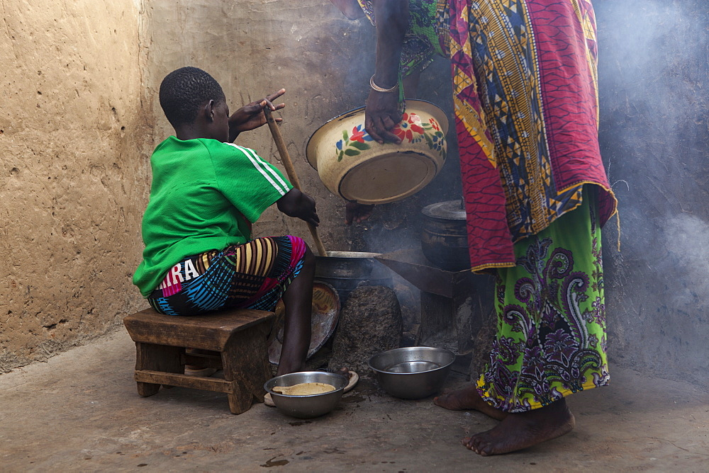 A young girl helping her mother cook at their home in Tinguri, Ghana, West Africa, Africa