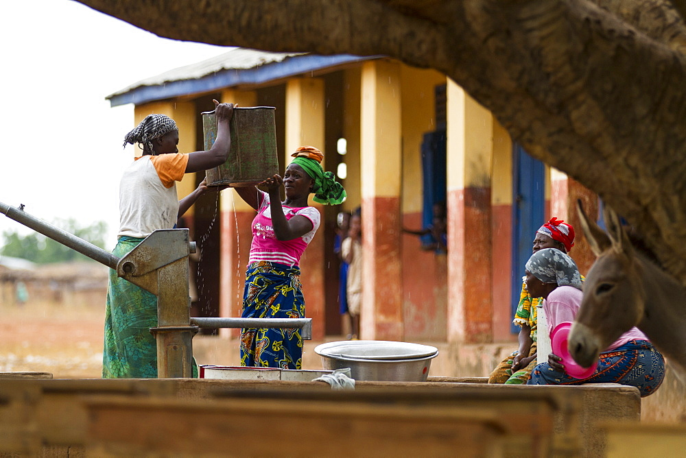 Women collecting water from one of the community water pumps in Tinguri, northern Ghana, West Africa, Africa