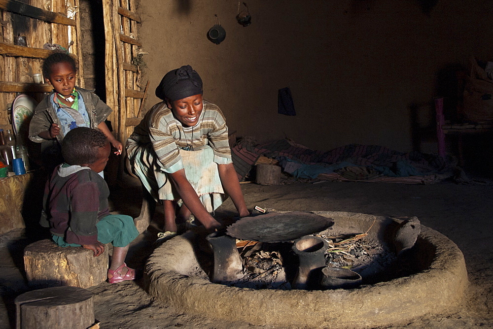 A woman lighting a fire in her home so she can cook dinner, Ethiopia, Africa