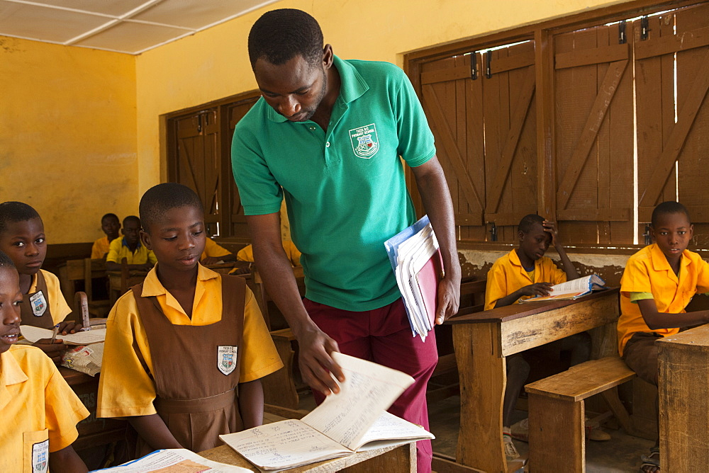A male teacher teaching a classroom of children at a primary school in Ghana.