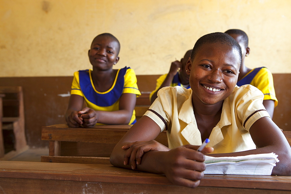 A portrait of a school girl smiling during a lesson in her classroom.