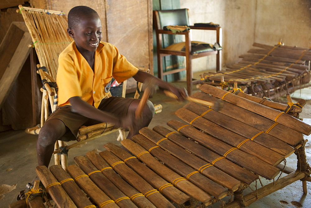 A school boy playing music on a large wooden xylophone at his primary school in Ghana.