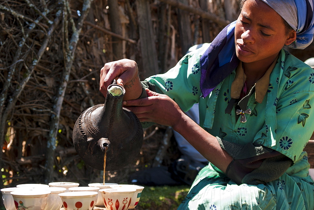 A woman pouring coffee from a traditional Ethiopian coffee pot, Ethiopia, Africa