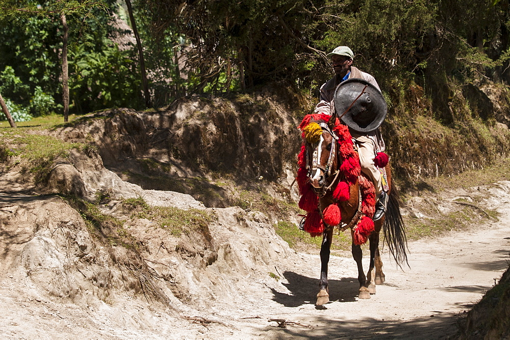 A man riding a horse with traditional red and yellow Ethiopian headdress and carrying a traditional round shield.