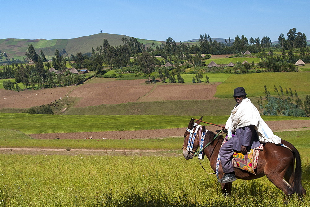 A man on horseback with a beautiful view of the rolling hills of rural Ethiopia, Africa
